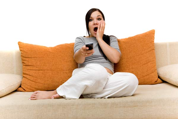 Girl watching TV on sofa, shocked